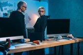 několik hackerů stojící poblíž stůl s počítači v temné místnosti