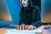 Fotografia primo piano sparato di hacker mascherati femminile con i tatuaggi sulle mani lo sviluppo di malware