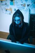Fotografia vista di alto angolo di giovane femmina hacker lo sviluppo di malware sotto luce blu