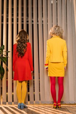 rear view of women in bright clothing standing at window at colorful apartment, doll house concept