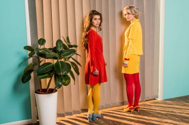 women in bright clothing standing at window at colorful apartment, doll house concept