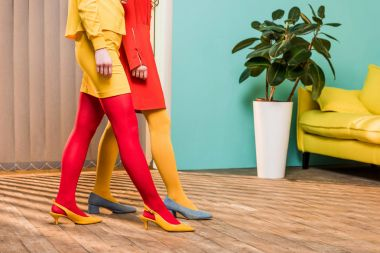 cropped shot of women in bright clothing at colorful apartment, doll house concept
