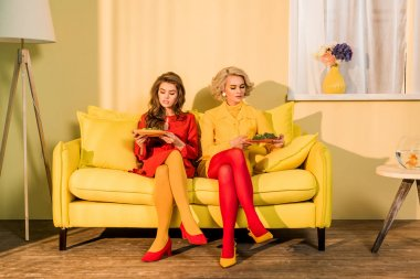 pretty women in retro clothing with vegetables on plates sitting on yellow sofa at bright room, doll house concept