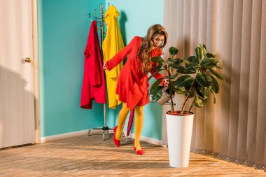old-fashioned girl in red dress watering plant with watering can at home