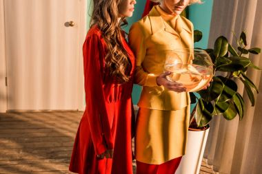 cropped image of retro styled girls in colorful dresses holding aquarium with fish at home