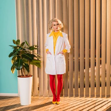 beautiful retro styled doctor standing in white coat and red tights in clinic