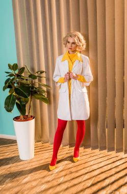 beautiful retro styled doctor posing in colorful dress and white coat in clinic