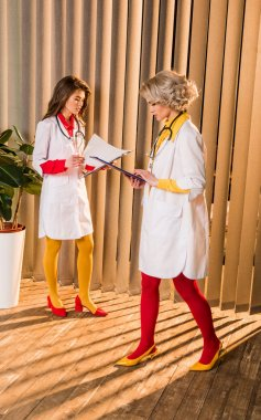 beautiful retro styled doctors looking at clipboards in clinic