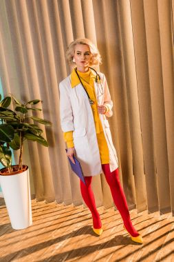 beautiful retro styled doctor in colorful dress standing with clipboard in clinic