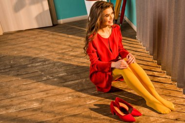 high angle view of smiling retro styled woman in red dress sitting on floor and looking at jalousie at home