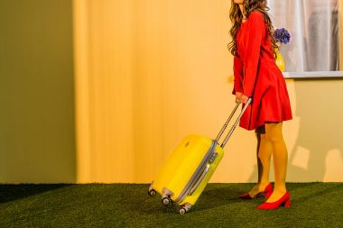 cropped image of retro styled woman in red dress standing with yellow wheeled bag at home, travel concept