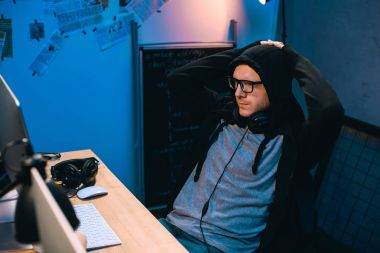hooded hacker relaxing on chair in front of his workplace
