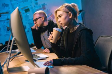 young female hacker drinking coffee and working on malware with accomplice