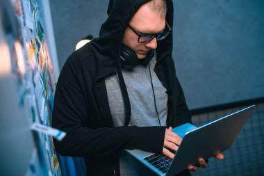 hooded hacker developing malware with laptop in dark room