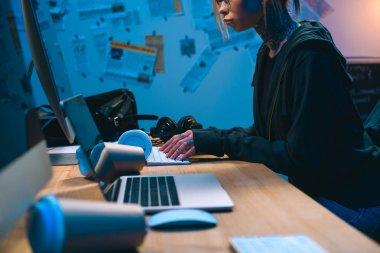 cropped shot of female hacker developing malware in dark room