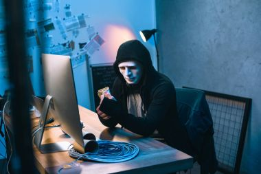 hooded hacker in mask counting stolen money at his workplace