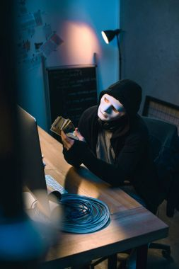 hacker in mask counting stolen money at his workplace