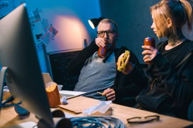 young hackers drinking beer and eating junk food while working on malware
