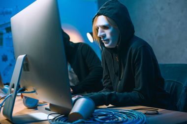 hacker in mask working with computer to develop malware
