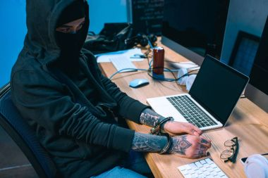 busted hacker in mask with handcuffs in front of workplace