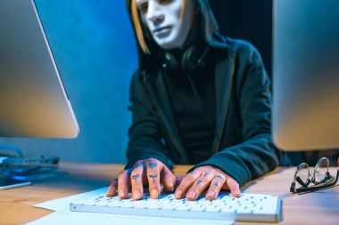 close-up shot of masked female hacker with tattoos on hands developing malware