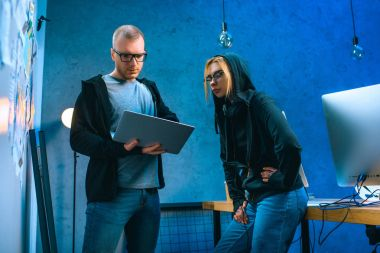 couple of hackers with laptop in dark room