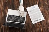 Oříznout záběr robota pracovat s notebookem na dřevěný povrch s obchodní kontrakt