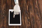 Fotografia ritagliata colpo di robot utilizzando la tavoletta digitale su superficie di legno