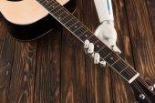 Oříznout záběr robota hrál na akustickou kytaru přes dřevěný povrch