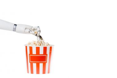 Cropped shot of robot taking popcorn out of bucket isolated on white stock vector