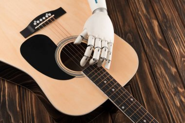 cropped shot of robot touching strings of acoustic guitar over wooden surface