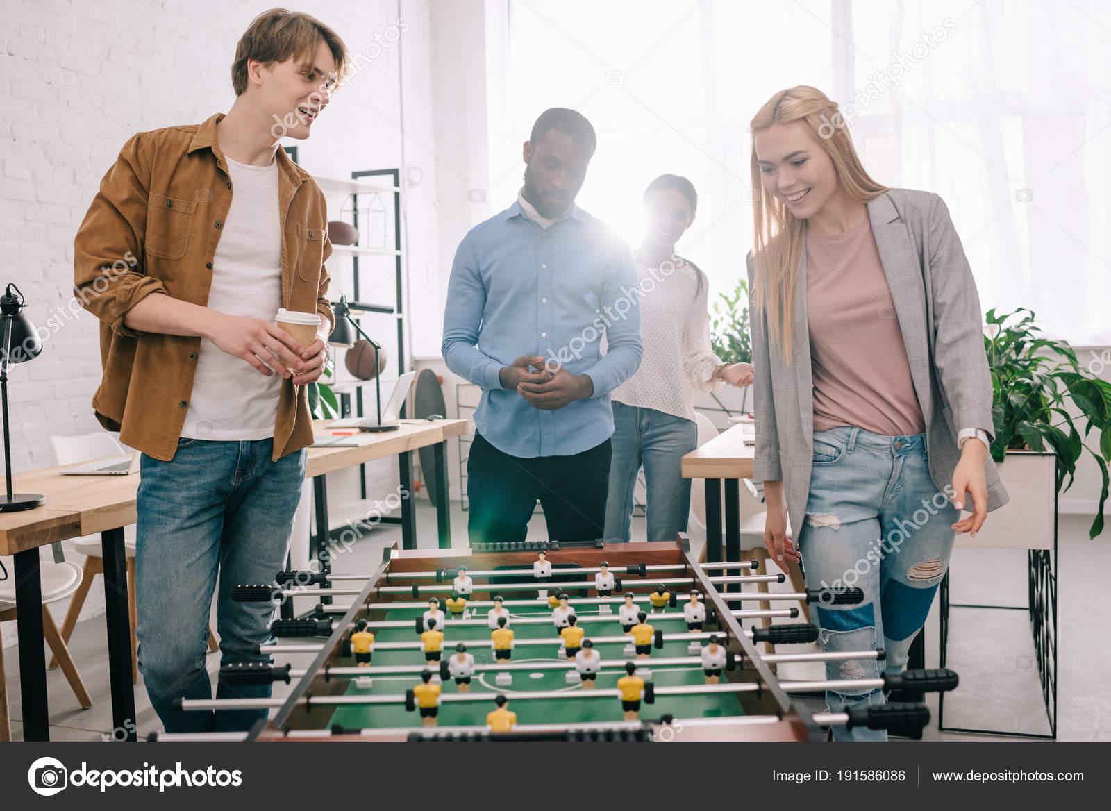 Souriant multiethnique businesspeople aller pour jouer baby foot