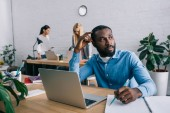 Photo thoughtful african american businessman sitting at table and coworkers working behind in modern office