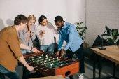 multiethnische Geschäftsleute spielen Tabelle Fußball und weibliche Kollegen sie Aufmunterung
