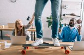 Photo cropped image of businessman riding on longboard on table and shocked colleagues in modern office