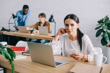 businesswoman with smartphone and colleagues working behind in modern office