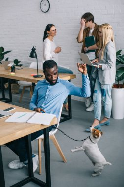 african american businessman playing with dog on leash and coworkers having meeting behind in modern office