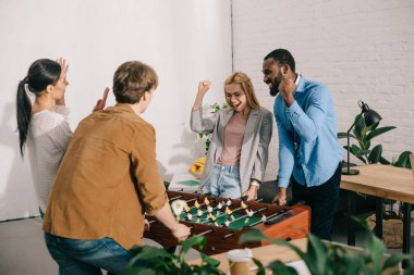 happy multicultural business colleagues gesturing and playing table football in modern office