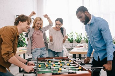 side view of happy multicultural businessmen playing table football in front of celebrating and gesturing female colleagues