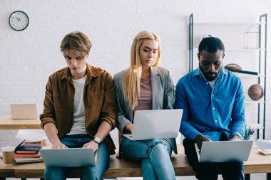 dizüstü bilgisayarlar kullanarak ve modern ofisindeki masada oturan üç çok kültürlü iş arkadaşları