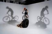 Fotografia giovane motociclista prova in casco bilanciamento sulla ruota del trattore