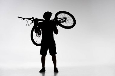 silhouette of trial biker holding bicycle on shoulders on white