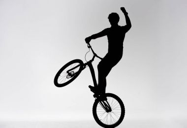 silhouette of trial biker standing on back wheel and raising hand on white
