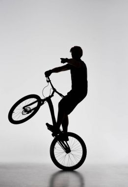 silhouette of trial biker standing on back wheel and pointing somewhere on white