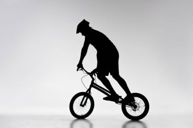 silhouette of trial cyclist balancing on bicycle on white
