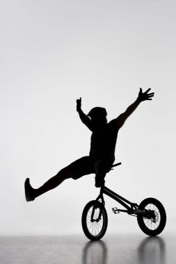 silhouette of trial biker sitting on handlebars of bicycle on white