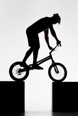 silhouette of trial cyclist balancing on two stands on white