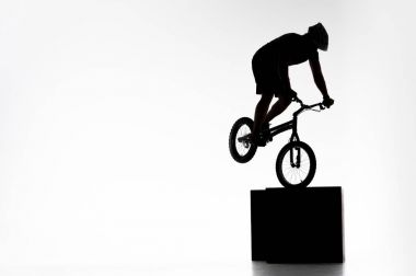 silhouette of trial cyclist performing stunt while balancing on cube on white