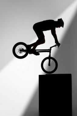silhouette of trial cyclist performing stunt while balancing on cube on grey