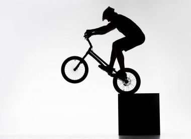 silhouette of trial cyclist performing back wheel stand while balancing on cube on white